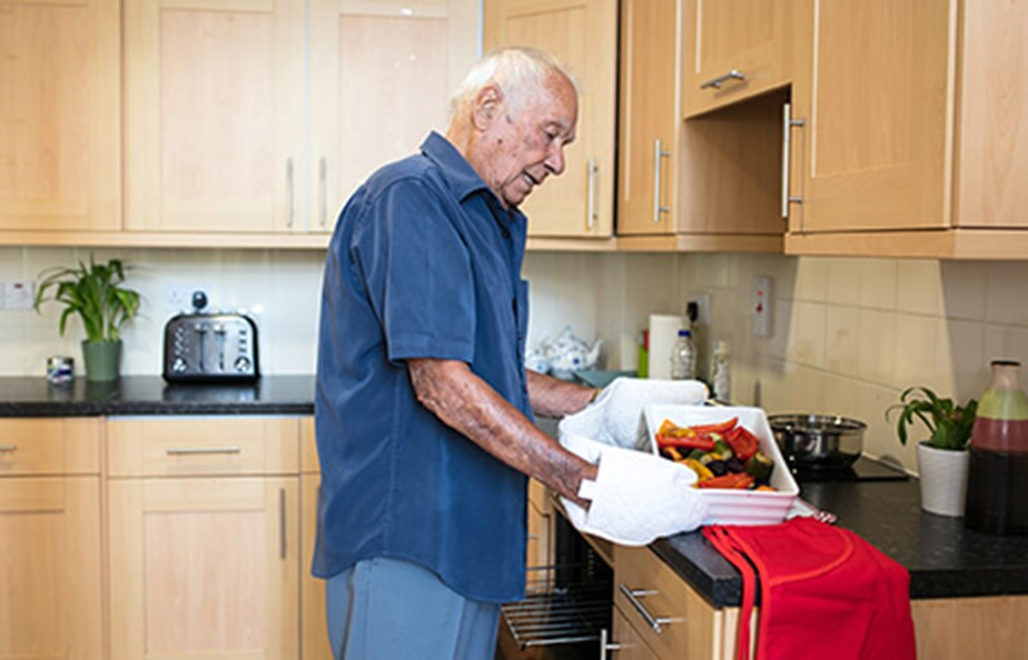 Man getting food out of oven