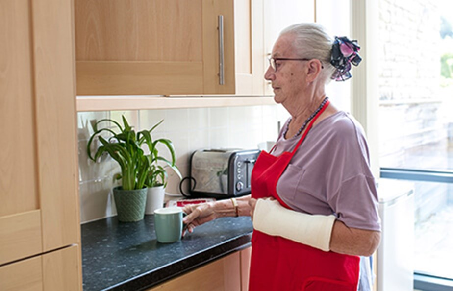 Woman with plaster on arm making a hot drink in a kitchen