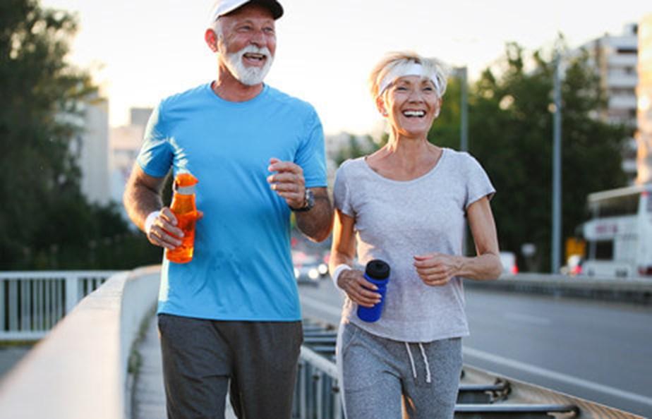 Senior Man And Woman Jogging Along Roadside