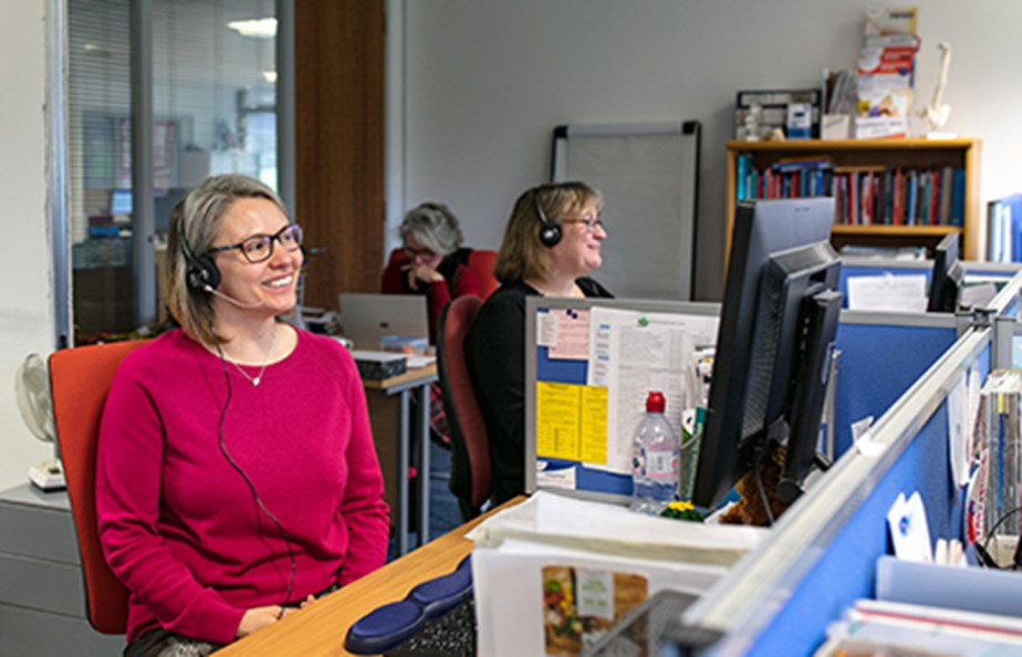 Woman smiling and speaking on telephone using a headset